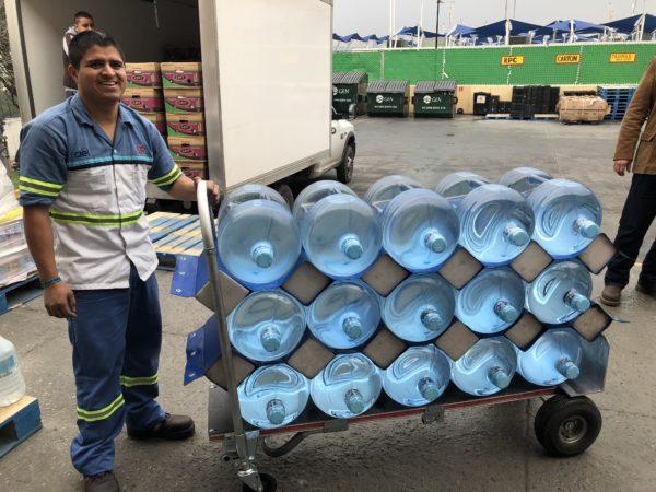 smiling man unloading full cart with bottle hammock
